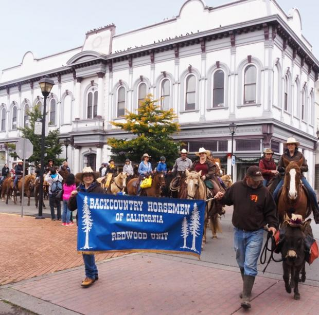 The Backcountry Horsemen of California parade through Old Town Eureka to deliver food donations to Food for People